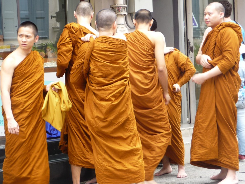 Young monka change their robes on the street outside temple