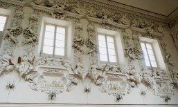 Allegorical statues on ledges with putti playing around them.